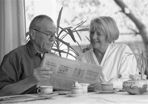 Seniorenpaar zuhause, lesen Zeitung am Fruehstueckstisch